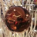 Braune glänzende Weihnachtskugel vor Weihnachtsdeko.