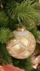 Goldene Weihnachtskugel am Tannenbaum mit schönen Verzierungen.