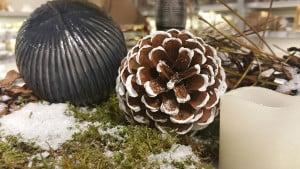 Graue Weihnachtskugel mit Tannenzapfen und Kerze auf Schnee-Moß-Dekoration