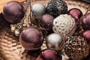 Lila Weihnachtskugeln in einer Dekoschale mit silbernen und schwarzen Christbaumkugeln.