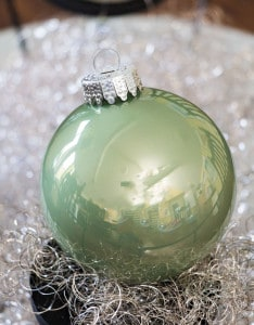 Weihnachtskugel in der Farbe Pastell Grün auf silbernen Engelshaar.