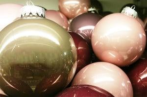 Weihnachtskugeln in verschiedenen Pastellfarben: Gold, Rosa, Lachs, Rot