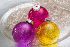 Drei Weihnachtskugeln mit leuchtenden Farben. Gelb, violett und pinke Kugeln.