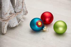 Drei Weihnachtskugeln in den Farben rot, blau und grün als Tisch-Dekoration.