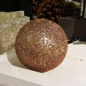 Glitzernde Bronze Weihnachtskugel auf einem Dekotablet.