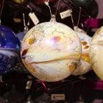 Kunstvoll verziehrte Weihnachtskugel mit verschiedenen Farbeffekten.