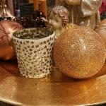 Weihnachtskugeln in Braun, Gold und Kupfer auf weihnachtlichem Dekoteller.