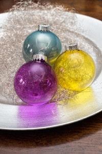 Transparente Weihnachtskugeln in den leuchtenden Farben Lila, Gelb und Petrol.
