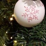 Weiße Weihnachtskugel mit rosa Verzierung am mit Lichterketten geschmückten Baum